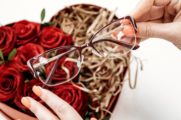 Glasses store concept  glasses on background of red roses  glasses in hand of ophthalmologist