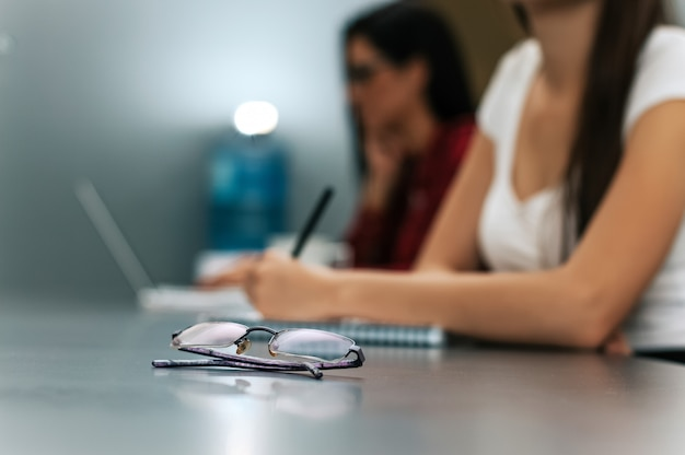 Glasses on table, businesswomen in background. business concept.