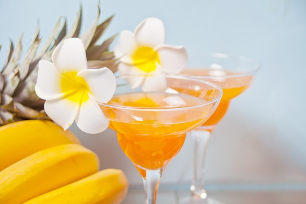 Glasses of tropical exotic multifruit juice cocktail drink with plumeria frangipani flower. troical beach picnic concept.
