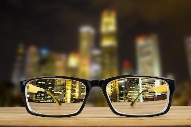 Очки рассматривают точку зрения фокуса зрения в ночном городе.