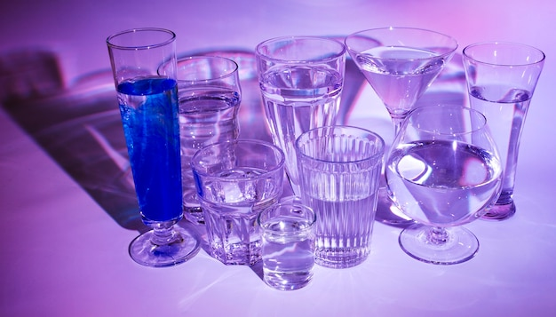 Glasses of water with blue cocktail on colored backdrop