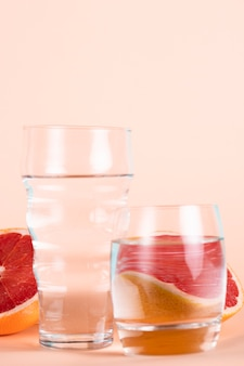 Glasses of water with half red oranges
