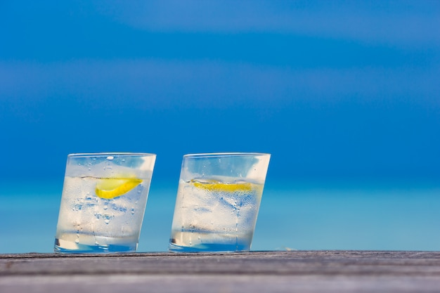 Glasses of waters with lemon on wooden on sea background