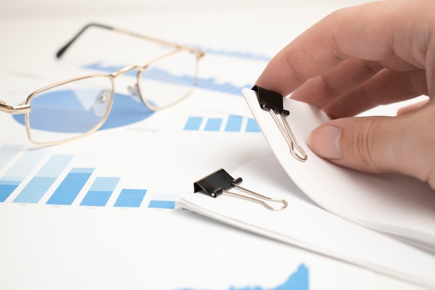 The glasses were placed on the data report documents, graphs and charts for preparation of the business plan.