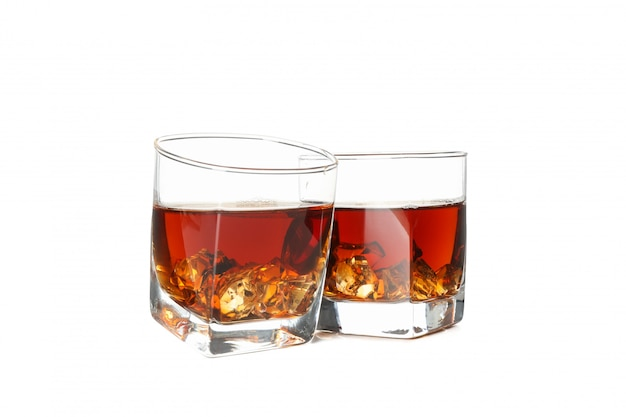 Glasses of whiskey with ice cubes isolated on white background