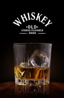 Glasses of whiskey with ice cubes on wood background