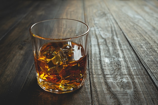 Glasses of whiskey with ice cubes on wood.