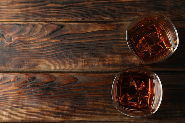 Glasses of whiskey with ice cubes on wooden background, top view