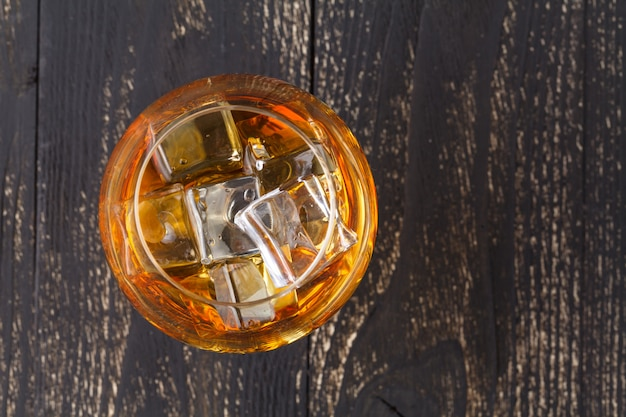 Glasses of whiskey on wood surface