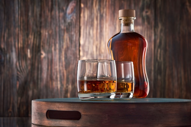 Glasses of whisky and a bottle on the wooden table