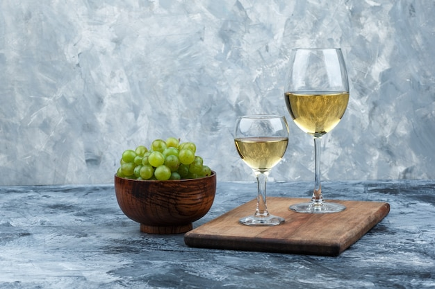 Glasses of whisky on a cutting board with bowl of white grapes close-up on a dark and light blue marble background