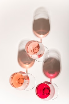 Glasses of white and pink wine with their shadows
