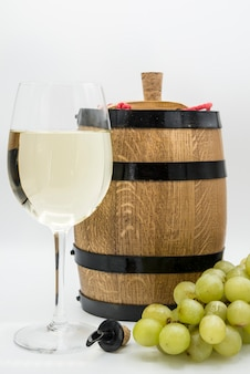 Glasses of white wine and wooden barrel