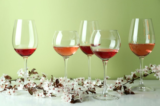 Glasses of wine and cherry flowers against green background