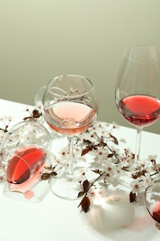 Glasses of wine and cherry flowers on white table