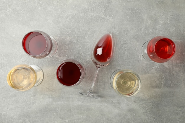 Glasses of wine on gray background, top view