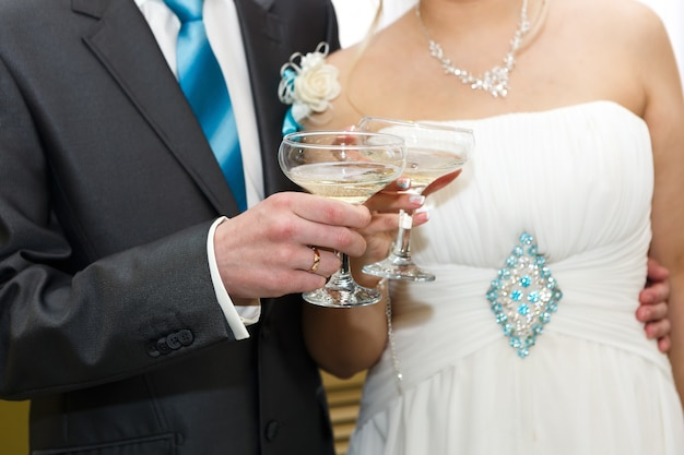 Glasses of wine in the hands of the bride and groom at a wedding party.