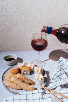 Glasses of wine with japanese sushi rolls served on plate on gray background
