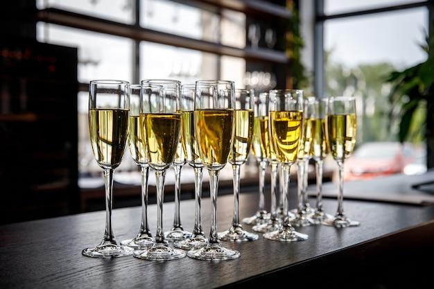 바 또는 이벤트 케이터링에서 시원하고 맛있는 샴페인 또는 화이트 와인을 곁들인 안경