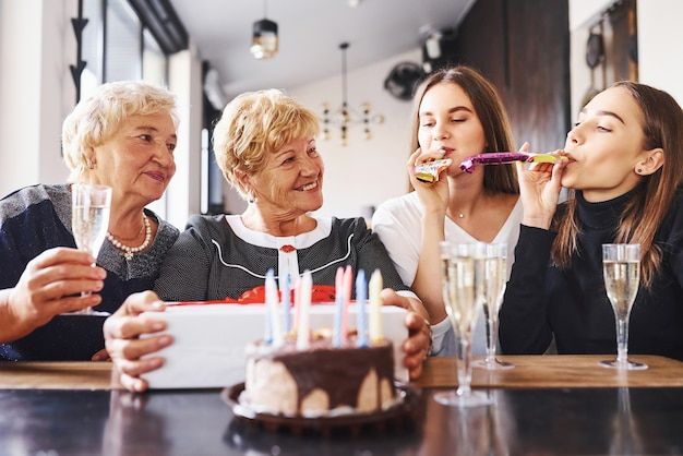 Glasses with alcohol in hands and cake on table. senior woman with family and friends celebrating a birthday indoors.
