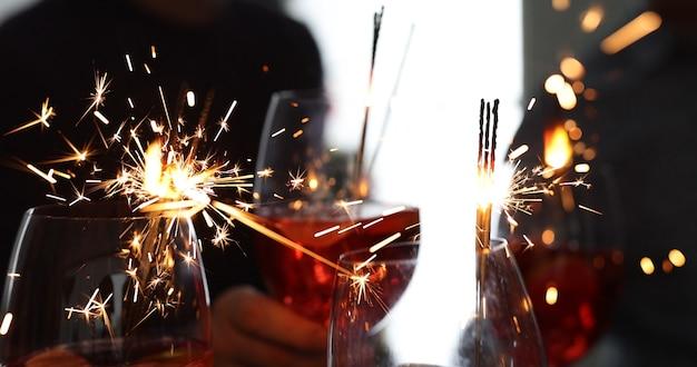 アルコールカクテルと線香花火のクローズアップグラス