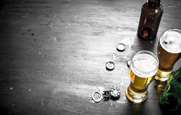 Стаканы с пивом, пробки и открывалка. на черной доске.