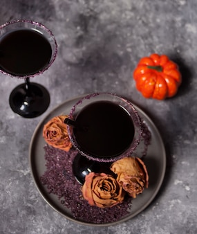 Glasses with black cocktail, dried roses and pumpkin for halloween party