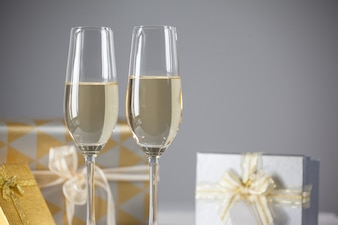 Glasses with champagne and gifts background