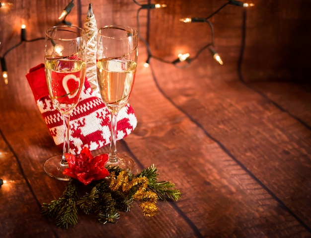 Glasses with champagne and christmas decoration background with space to write
