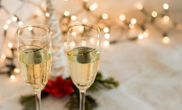 Glasses with champagne detail with christmas lights golden background