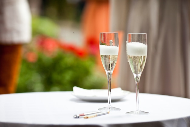 Glasses with champagne and foam stand on the white table