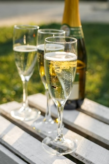 Glasses with champagne on green blurred background