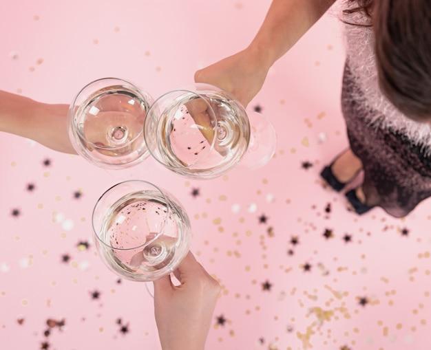 パーティーの上面図で女の子の手にシャンパンとグラス