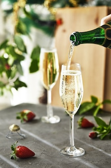 Glasses with champagne and strawberries with green leaves in the background