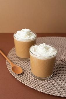 テーブルの上にホイップクリームとコーヒーとグラス