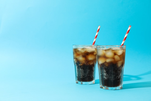 Glasses with cold cola and tubule on blue background, space for text