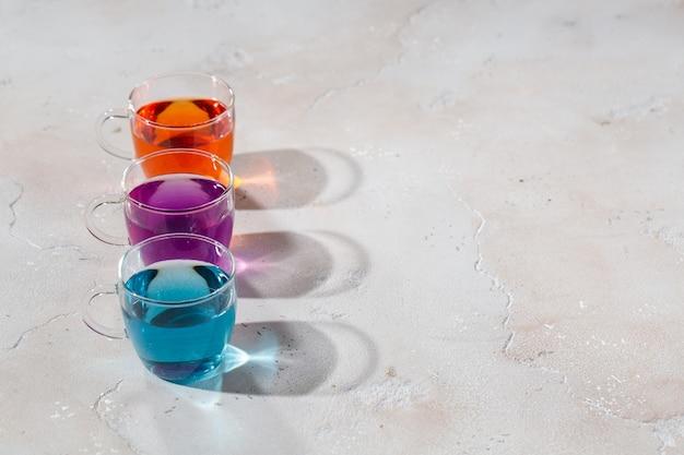 明るい大理石の背景に着色された液体とメガネ
