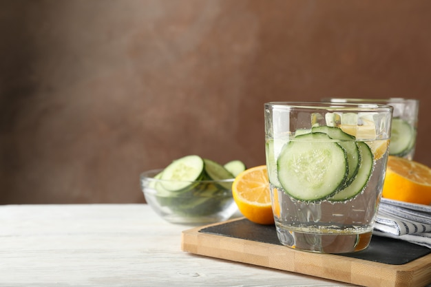 Glasses with cucumber water on board on wood background, close up