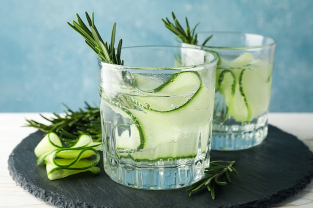 Glasses with cucumber water on tray on wooden table, close up