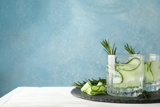 Glasses with cucumber water on tray on wooden table, space for text