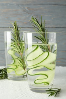 Glasses with cucumber water on white table