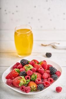 Очки с напитком и ягодами на деревенском фоне. фото высокого качества