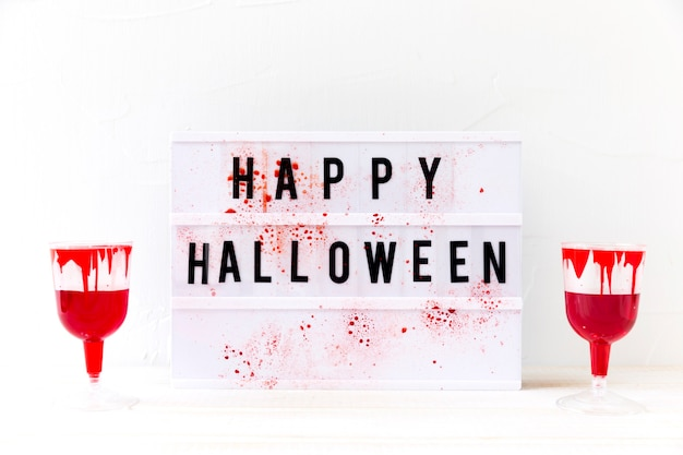 Glasses with fake blood near happy halloween writing