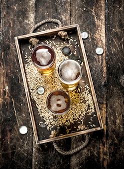 木製の背景の古いトレイに新鮮なビールとグラス