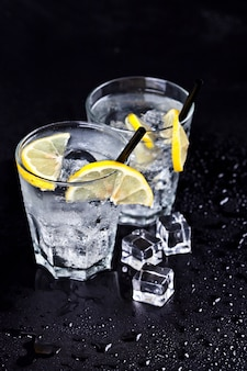 Glasses with fresh cold carbonated water with ice cubes and lemon slices