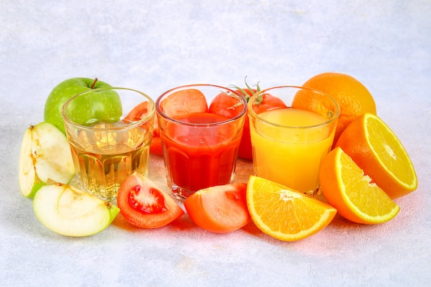 Glasses with fresh orange, apple, tomato juice on a gray concrete table.