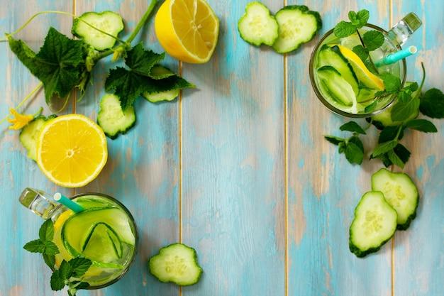 新鮮なオーガニックのグラス冷たくてさわやかな注入されたデトックス水とレモンとキュウリ上面図