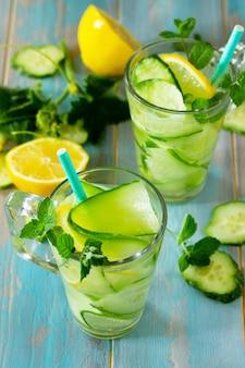 新鮮なオーガニックのグラス冷たくてさわやかな注入されたデトックス水とレモンとキュウリ