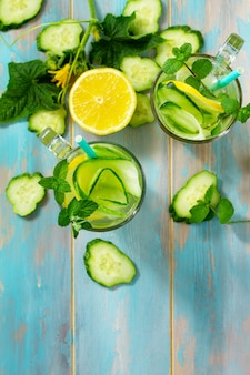 Glasses with fresh organic cold and refreshing infused detox water with lemon and cucumber top view