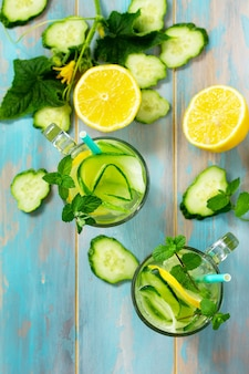 Glasses with fresh organic cold and refreshing infused detox water with lemon top view flat lay